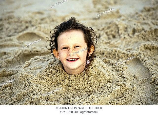Delighted young girl buried in the beach sand, Cape Cod, MA