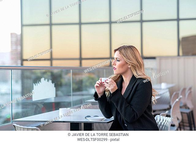 Businesswoman after work taking a coffee
