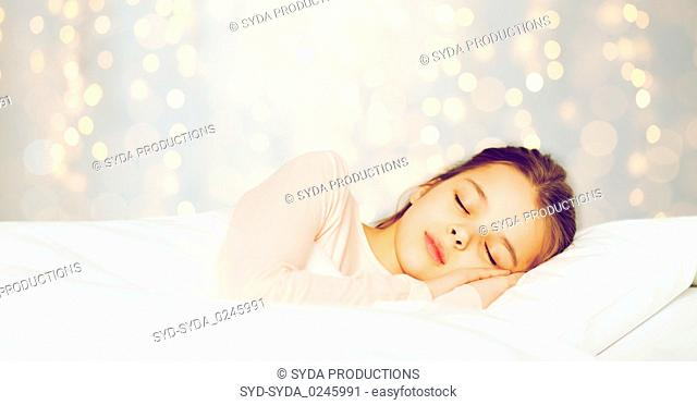 girl sleeping in bed over holidays lights