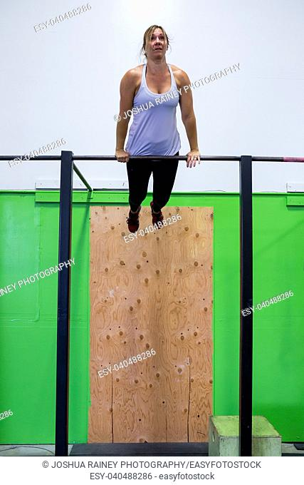 Fit woman doing exercises and pullups on a pullup bar at a crossfit gym for females