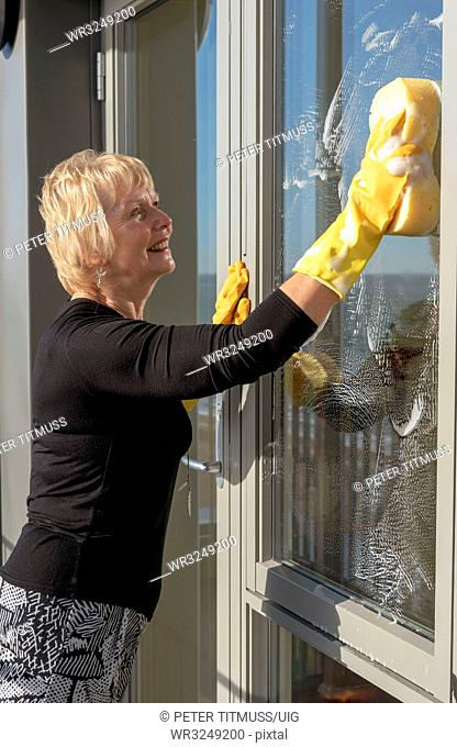 Woman cleaning outside of glass windows using a sponge and soapy water