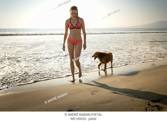 Young attractive woman in bikini walking with Golden Retriever dog at beach. Riviera Nayarit, Mexico