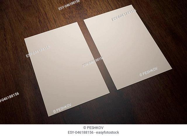 Two blank white paper sheets on wooden desktop. Mock up, 3D Rendering