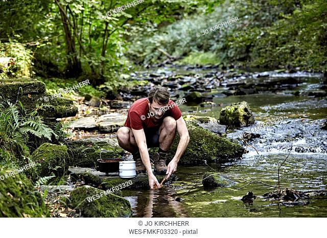 Man washing dishes at a river