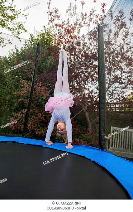 Girl on trampoline wearing tutu doing handstand