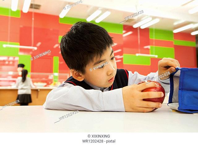 School boy checking lunch bag in school cafeteria