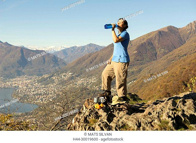 Woman Drinking Water From Bottle On Mountain Top in Ticino, Switzerland