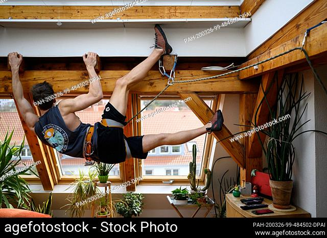 26 March 2020, Baden-Wuerttemberg, Stuttgart: Climber Niklas hangs for fun in his climbing gear on a roof beam in the living room of the apartment where his...