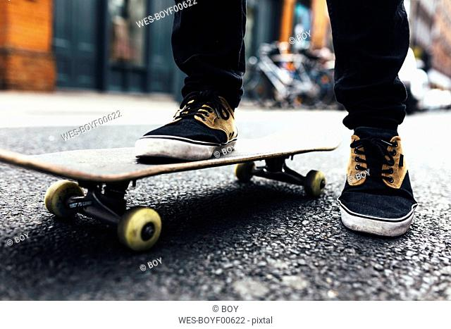 Young skateboarder on the street, partial view