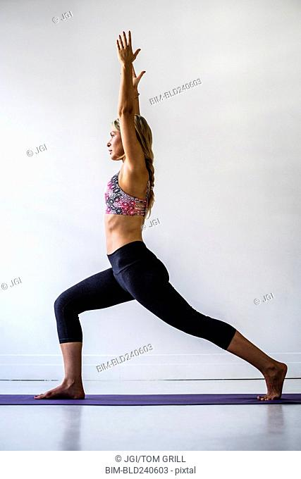 Mixed Race woman stretching in yoga pose