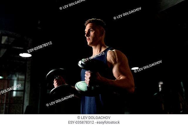 sport, bodybuilding, fitness and people concept - young man with dumbbells flexing muscles in gym