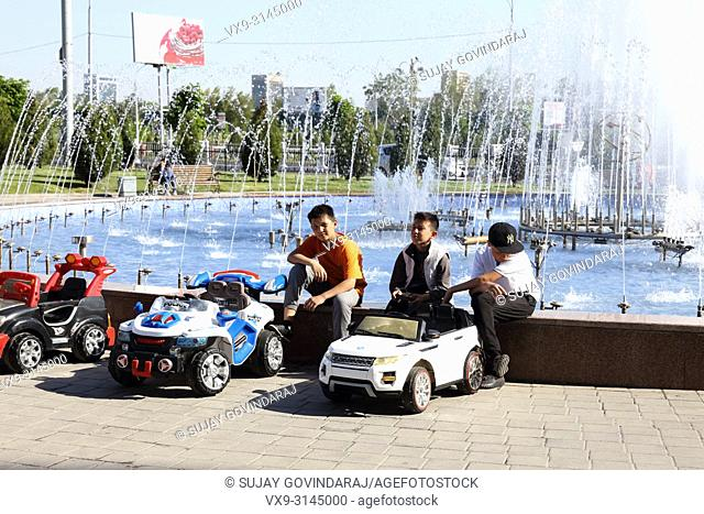 Tashkent, Uzbekistan - May 01, 2017: Three unknown boys offers toy car rentals on an occasion of fountains day in the city