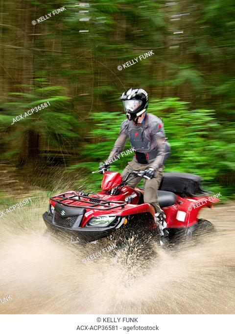 A single male ATV quad bike rider races through water near Powell river on the upper Sunshine coast of the Vancouver coast and mountain range, British Columbia