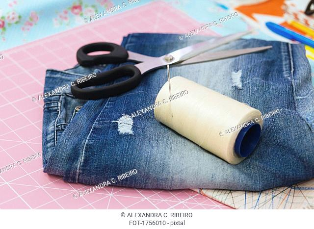 Close-up of spool and scissors with jeans on cutting mat