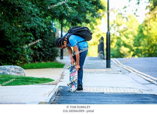 Boy checking his skateboard on sidewalk