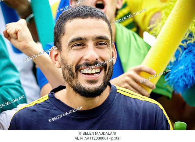 Man smiling cheerfully at football match, portrait