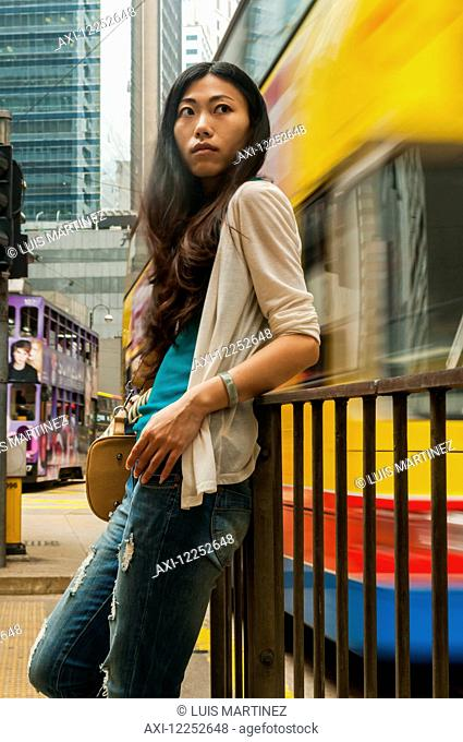 Chinese young woman in a busy, urban centre; Hong Kong, China
