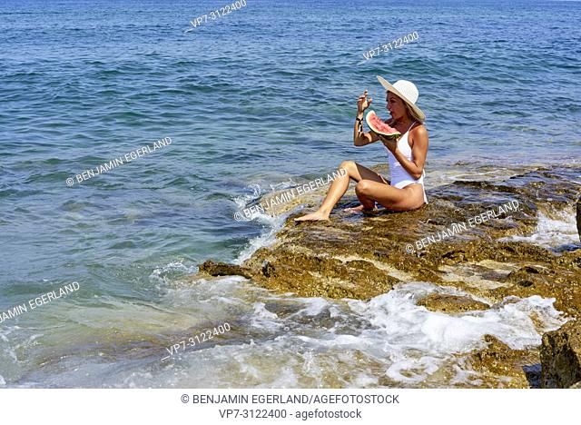 woman with water melon sitting on rock next to sea, holiday, summer, sunny, enjoying life, travel, healthy. Chersonissos, Crete, Greece