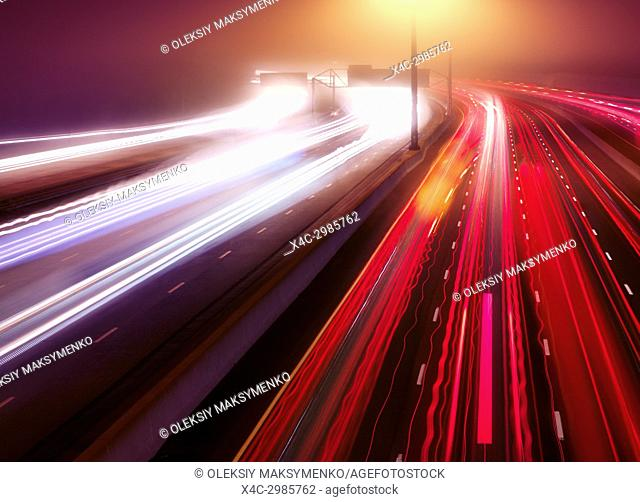Artistic abstract traffic light trails. Busy highway traffic on a misty night, Highway 401, Toronto, Ontario, Canada