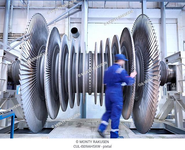 Engineer inspecting steam turbine blades in repair bay of workshop