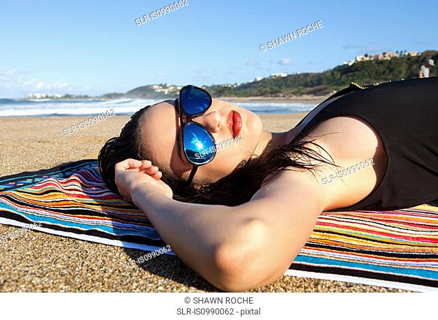 Woman lying on beach towel