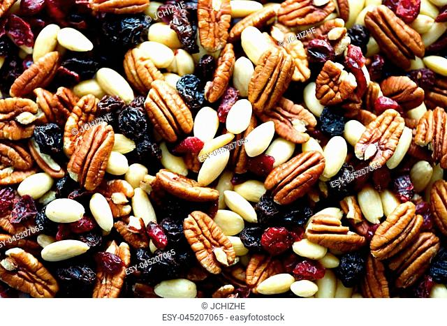 Mixed nuts and raisins in wooden bowl. Healthy food and snack. Walnut, pistachios, almonds, hazelnuts, cashews, raisins. Banner