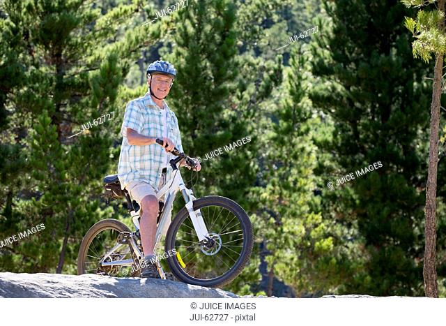 Older man riding mountain bike in forest