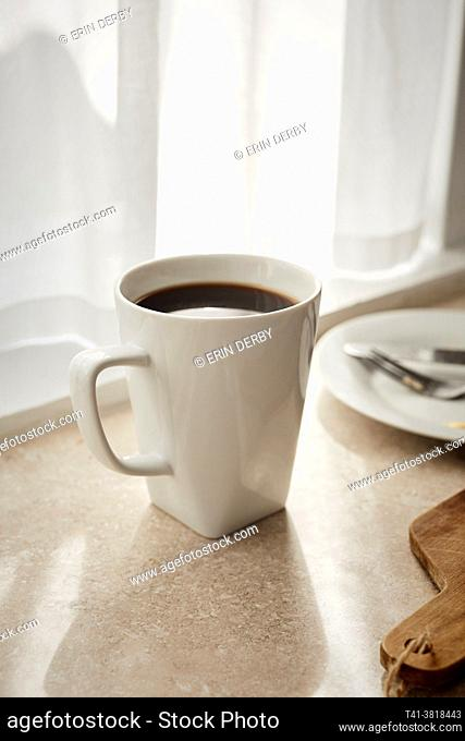 A white mug of coffee sitting on a counter of a sun streaked kitchen