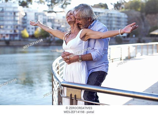Senior couple taking a city break, embracing at a railing