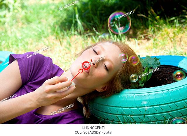 Woman lying on tire blowing bubbles