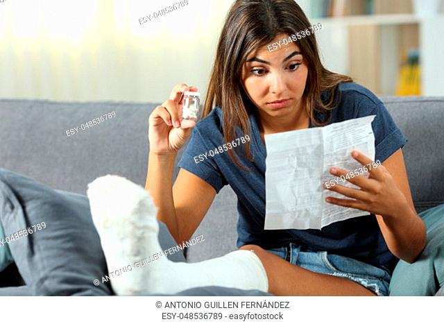 Confused disabled woman reading pill leaflet sitting on a couch in the living room at home