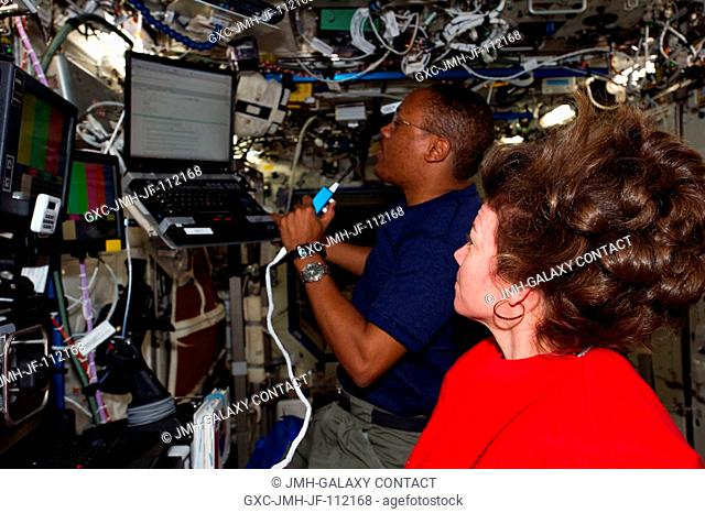 NASA astronauts Alvin Drew, STS-133 mission specialist; and Catherine (Cady) Coleman, Expedition 26 flight engineer, work in the Destiny laboratory of the...