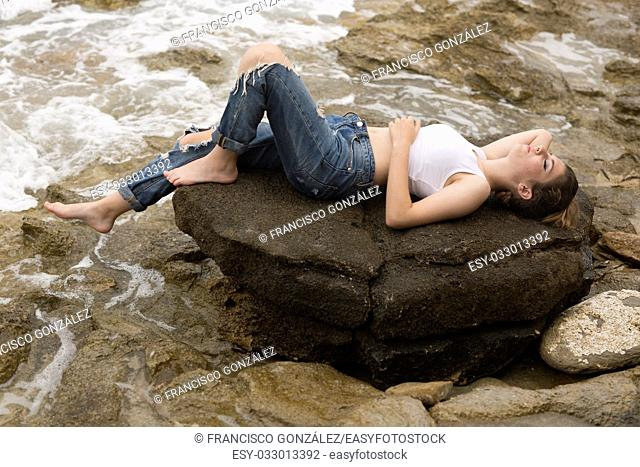Teenage girl lying on the rocks of a creek of Villajoyosa, in the province of Alicante, Spain