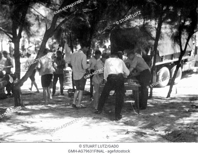 A group of soldiers gathered together while wearing civilian clothing, a small group if getting food from a table, an M35 military truck is parked nearby