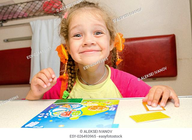 Little girl on the train with a happy smile sitting at a table on the lower second-class place car and makes the applique