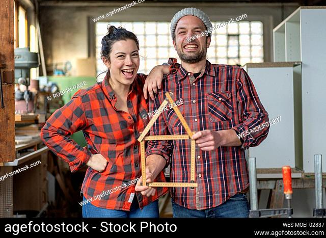Portrait of happy craftswoman and craftsman holding yardstick in their workshop