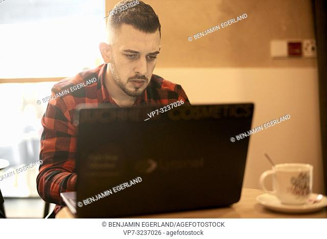 man working with laptop indoors in café, casual shirt, freelancer, self employee, Greek ethnicity, in Munich, Germany