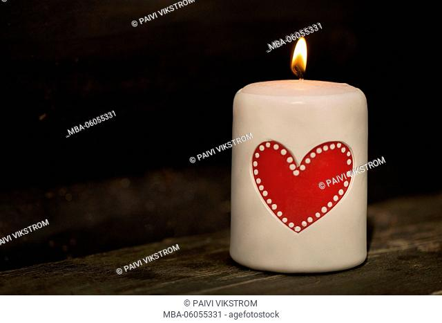 White table candle with red heart and flame
