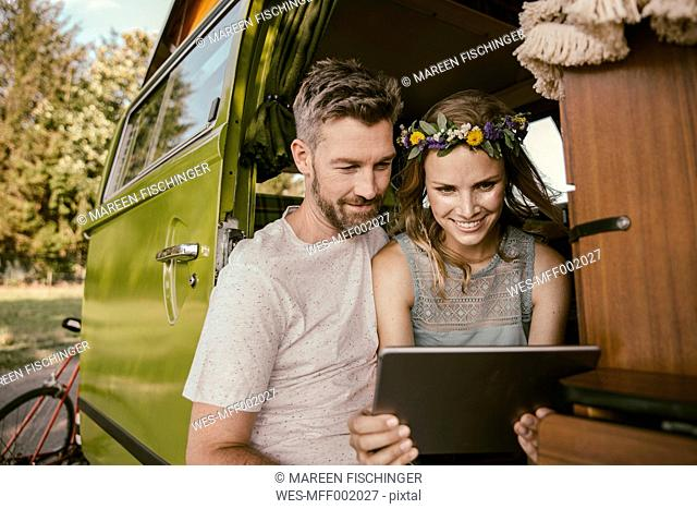 Couple looking at tablet computer in van