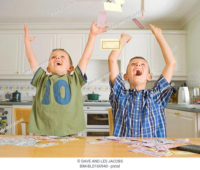 Caucasian brothers playing with toy money in kitchen