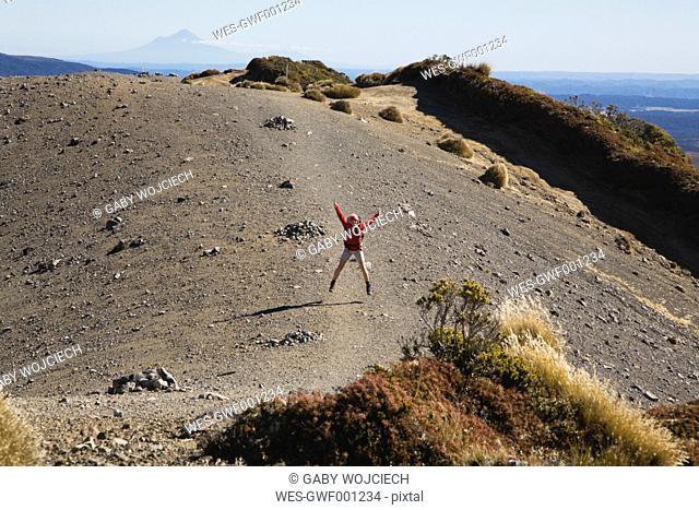 New Zealand, North Island, Woman jumping on volcanic moraine