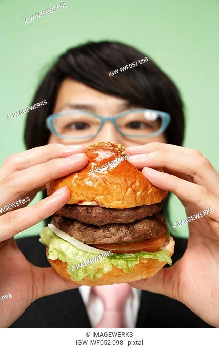Young man holding burger, close-up