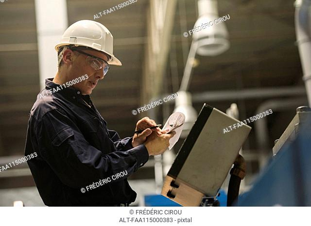 Factory worker examining control panel