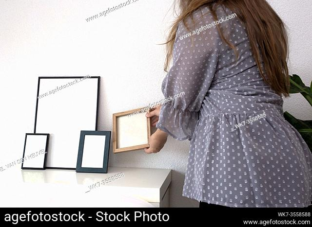 Woman holding empty photo or picture frame in a modern room near white wall, scandinavian design, retro interior space for text
