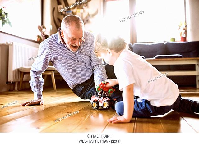 Grandfather and grandson playing at home with toys