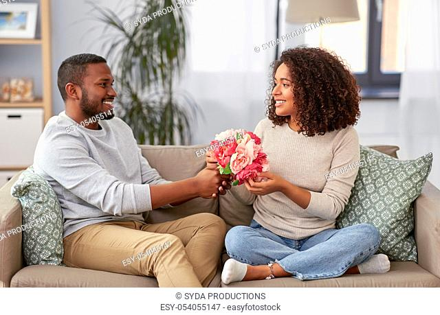 happy couple with bunch of flowers at home