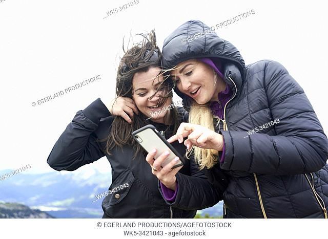 two friends using smartphone in windy weather conditions while hiking in mountains, Europe, Austria, Salzburg, Mount Untersberg