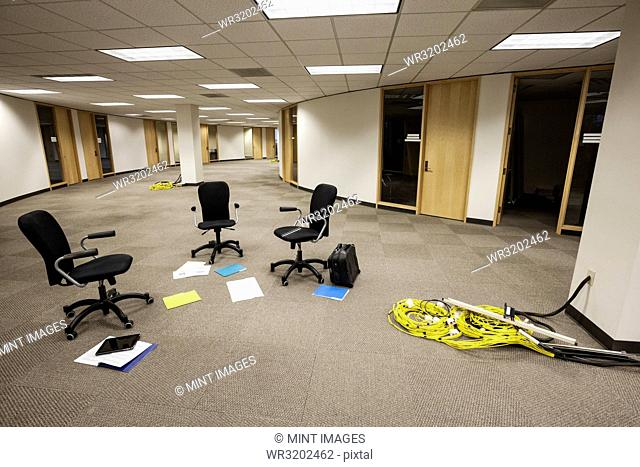 Three chairs sitting alone in an open area in an unoccupied office space