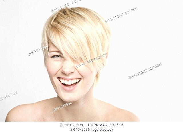 Young blond woman with short hair laughing into the camera