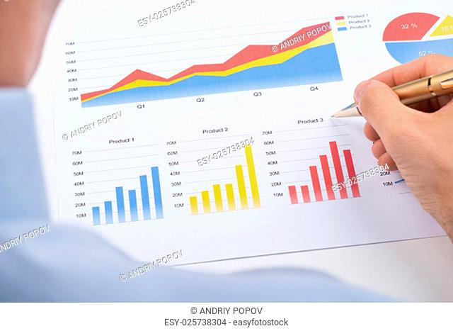 Close-up Of Businessperson Analyzing Colorful Graphs On Paper